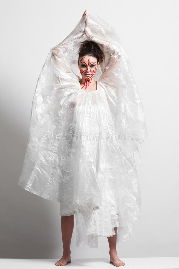 Model in a raincoat made of cellophane and in creative make-up. Studio photo session. White background stock images