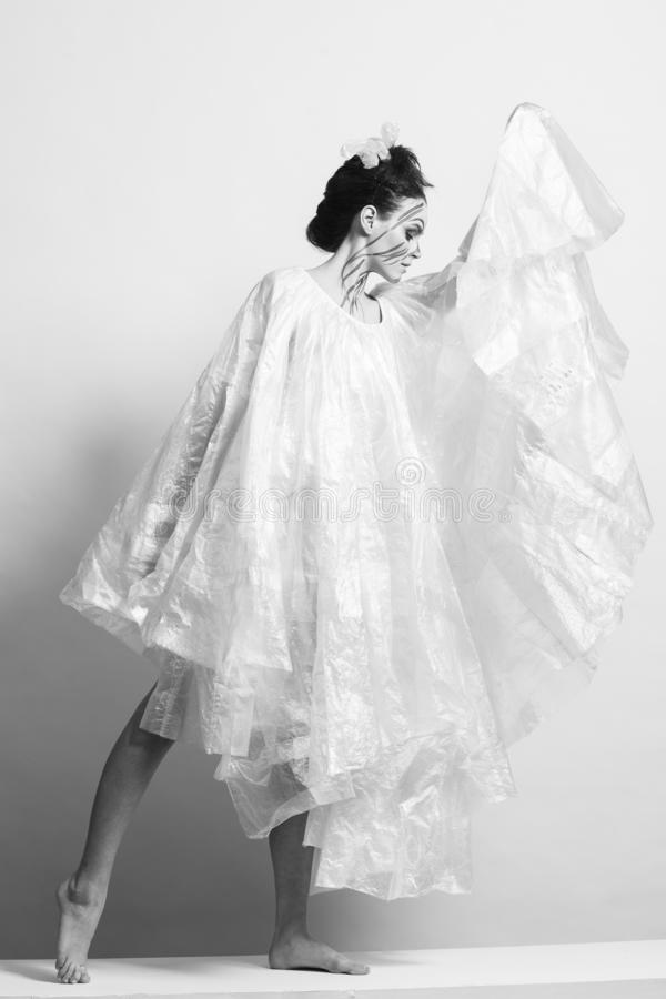 Model in a raincoat made of cellophane and in creative make-up. Studio photo session. White background royalty free stock photography