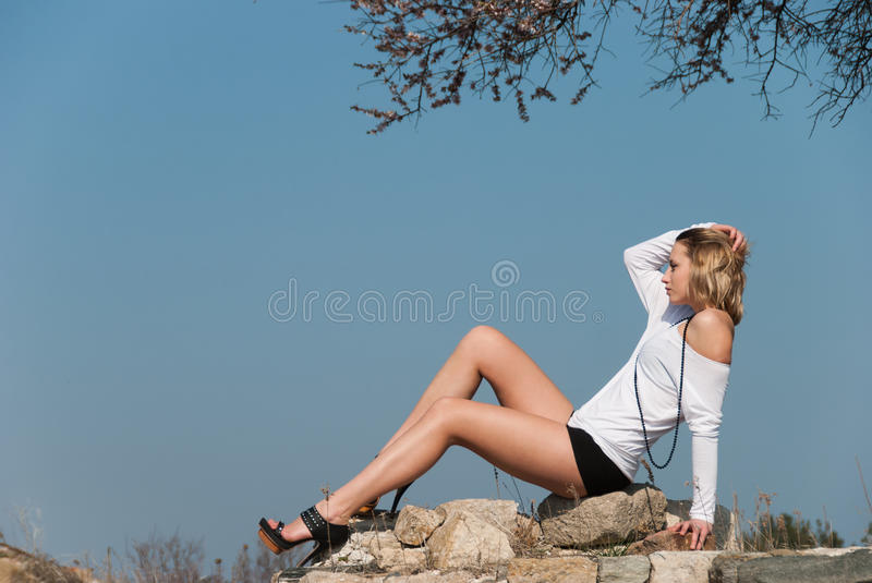 Model reclining on rocks, shows off her long legs. Model in profile reclining on rocks, shows off her long legs. Tall lady wearing heels, shorts and shirt stock photography