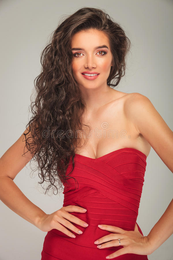 Model in red dress touching her waist while posing royalty free stock image