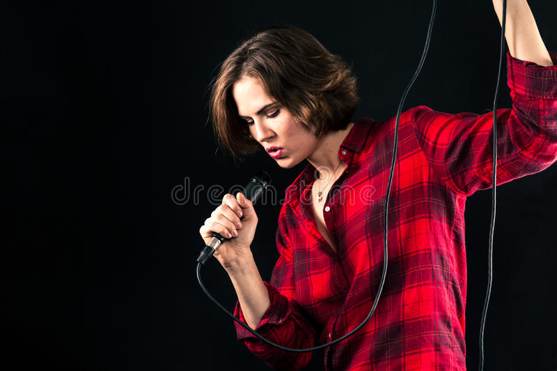 Model Red Flannel Shirt Singing Into Mic. Holding Cord stock photos