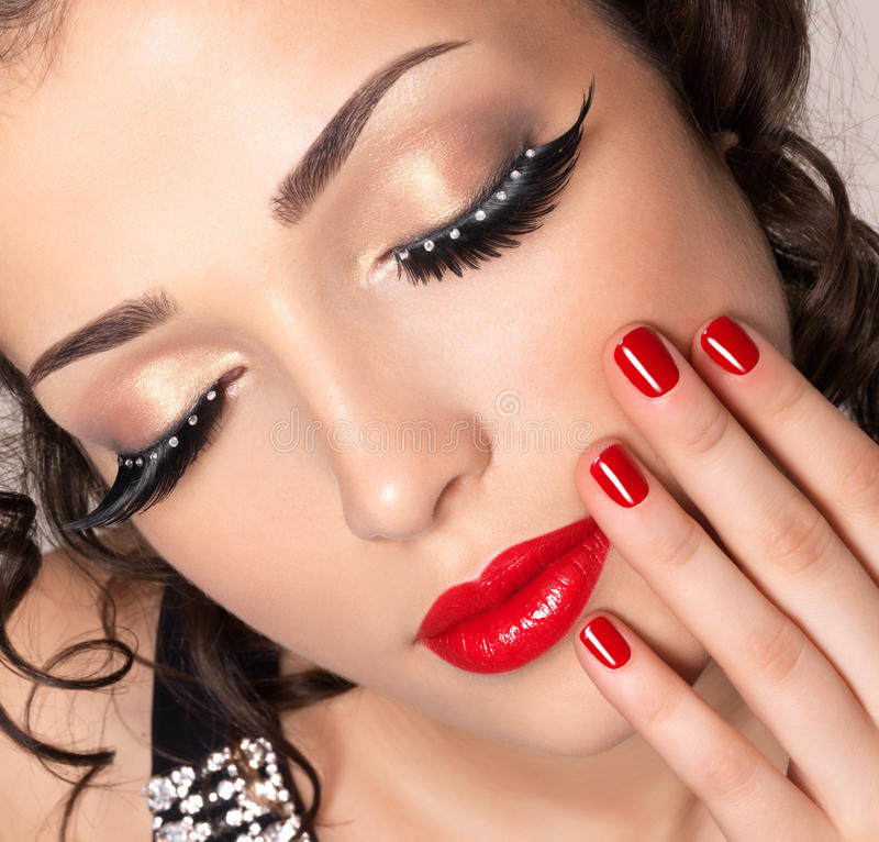 Model with red nails, lips and creative eye makeup. Beautiful fashion model with red nails, lips and creative eye makeup - isolated on white background royalty free stock image