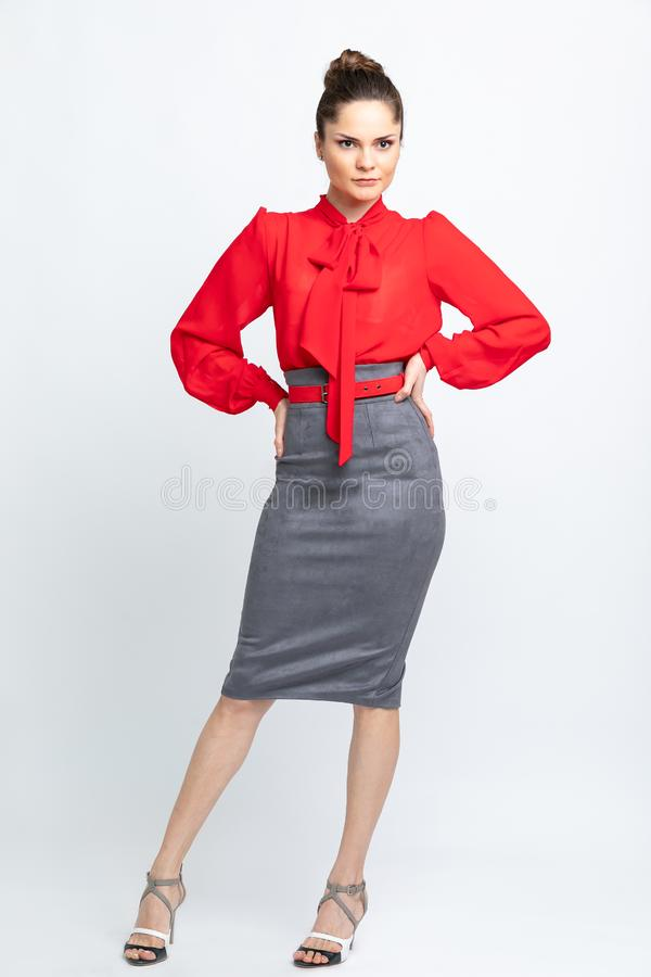Model in red shirt, grey suede skirt, red belt, white heeled sandals isolated on white background. stock photography