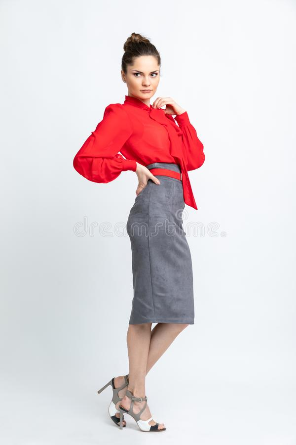 Model in red shirt, grey suede skirt, red belt, white heeled sandals isolated on white background. royalty free stock photography