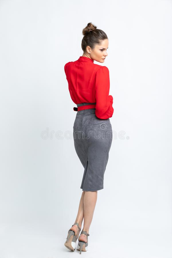 Model in red shirt, grey suede skirt with red belt, white heeled sandals isolated on white background royalty free stock images