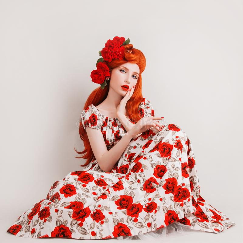 Model in rose flower dress. Beautiful stylish outfit. Long red hair. Redhead model with flower hairstyle on white background. Girl stock photography