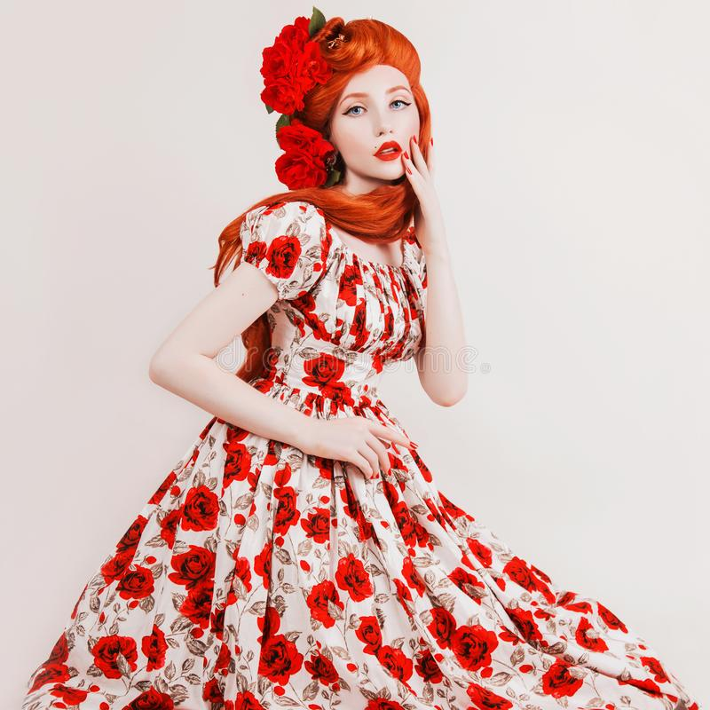 Model in rose flower dress. Beautiful stylish outfit. Long red hair. Redhead model with flower hairstyle on whitebackground. Girl. In bright outfit. Beauty stock photography