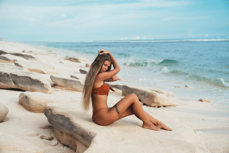 A model with a round succulent booty and lush breasts posing on a stone near the sea. The girl was walking on a white. Sandy beach and decided to stop for a royalty free stock photos