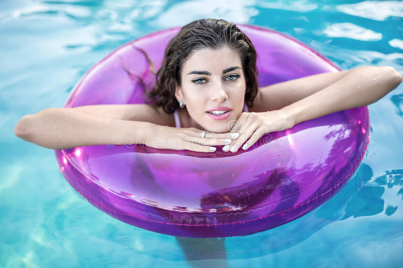 Model in rubber ring in swimming pool. Model with wet hair in a white swimsuit in the purple rubber ring in the swimming pool looks into the camera with parted royalty free stock photo