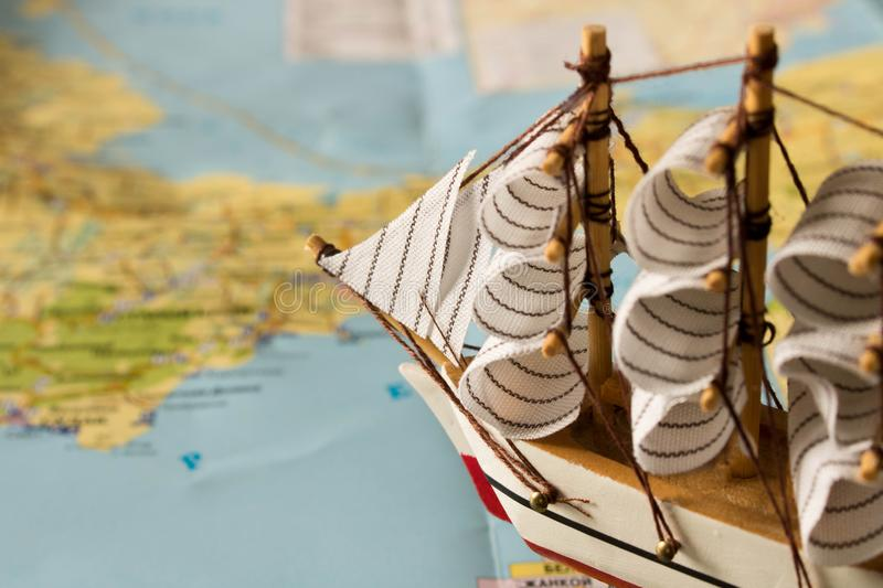 Model sailboat on the background of the map. Travel concept royalty free stock photography