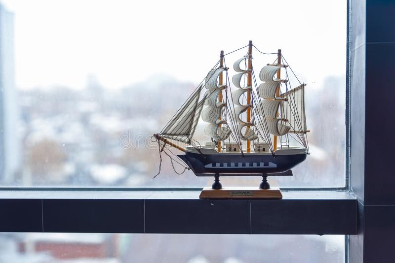 The model of a sailing ship stands on a misted window. The concept of travel. Dreams of a vacation. stock image