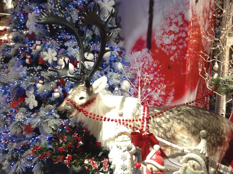 A model of Santa`s reindeer stands in front of a decorated christmas tree. stock image