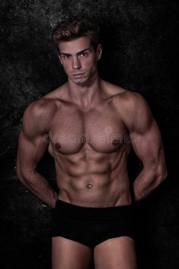 Model sexy mens in ondergoed, zwarte grungeachtergrond stock foto