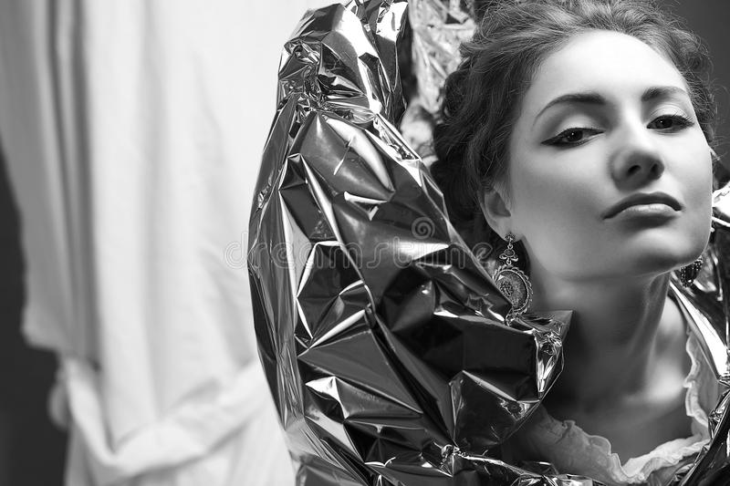 Model with silver foil. Arty portrait of a fashionable queen-like model with silver foil cape over white curtain background. close up. black and white studio stock images