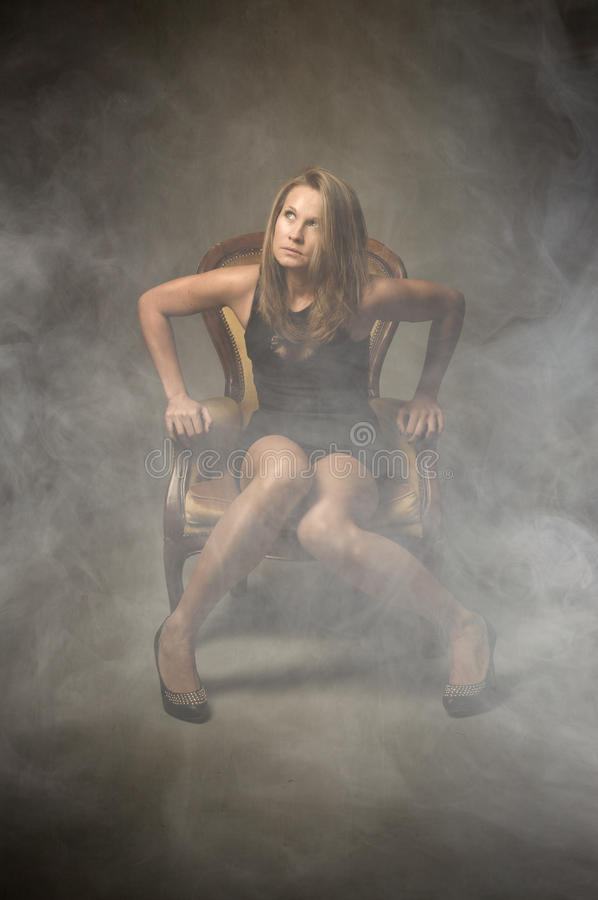 Model sit on yellow sofa royalty free stock photography