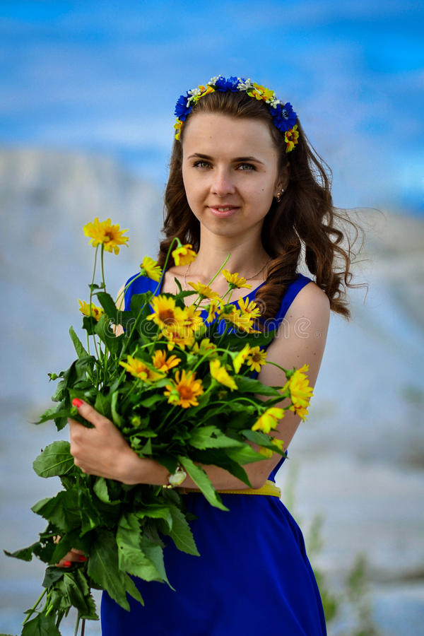 Beautiful cute girl in blue dress with bouquet of yellow stock images