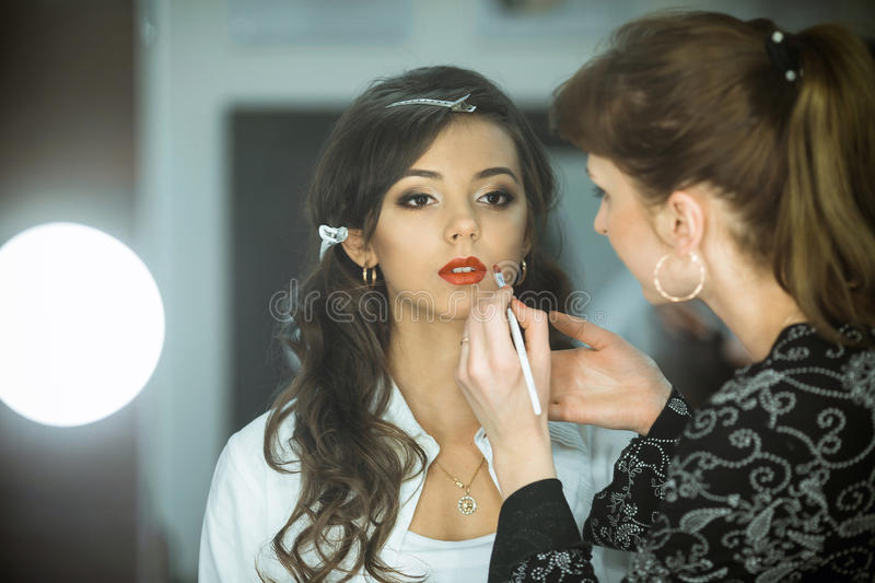 Professional makeup artist makes up lips beautiful, attractive model, celebrity. royalty free stock photos