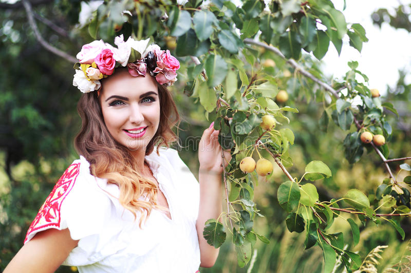 Model in slovakian national costume. Beautiful female model in slovakian national costume posing outdoor in flower head crown stock image