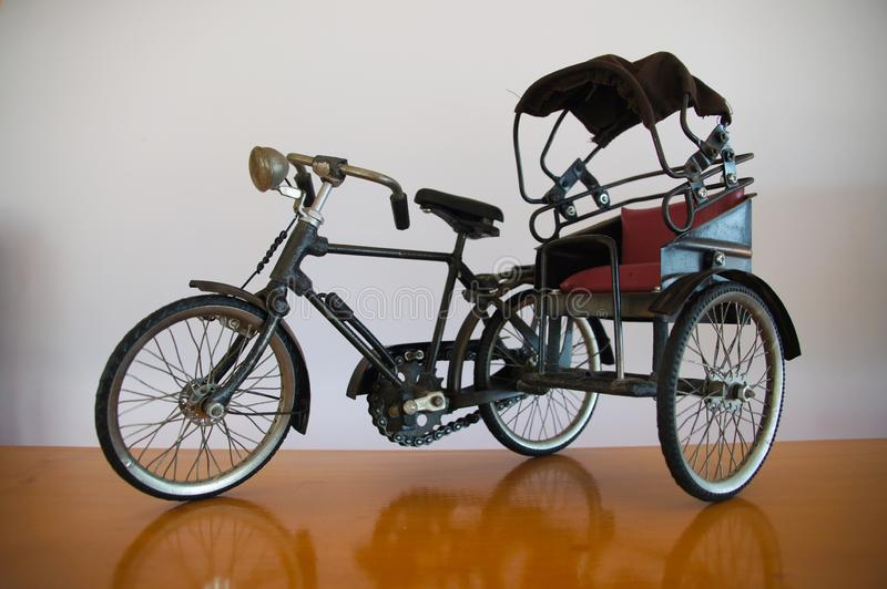 Model of a small tricycle in the olden days made of steel material and beautiful cloth. Background image stock photography