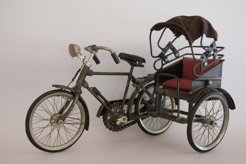 Model of a small tricycle in the olden days made of steel material and beautiful cloth. Background image royalty free stock photo
