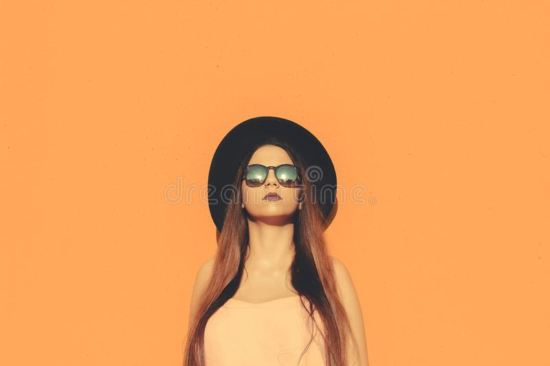 Fashionable girl standing wearing fashionable sunglasses and black hat with a solid color as background stock photography