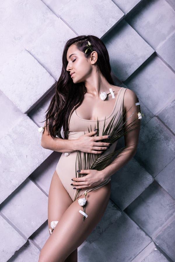 Radiant beauteous female model skillfully posturing in photo studio stock photo