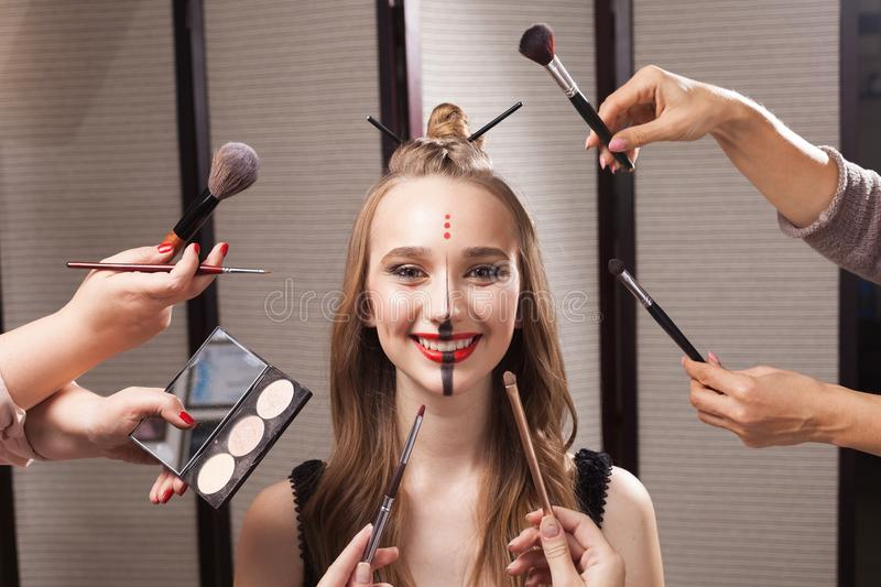 Model surrounded by hands holding brushes. Beautiful young model with professional unusual makeup and a coiffure with topknot and braid made by stylists in a stock photo