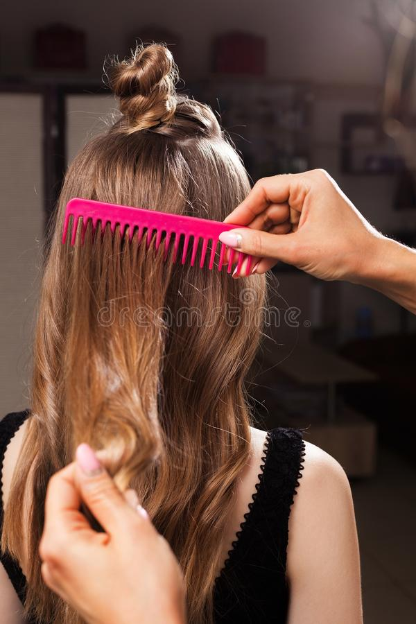 Model with a topknot having her hair being brushed. By a professional hairdresser using a pink brush in a beauty salon. concept of carefull hair treating stock image
