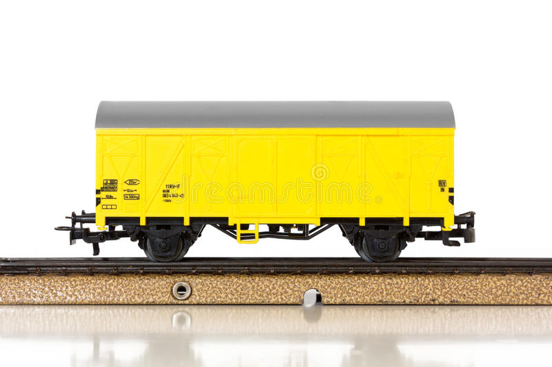 Model Train`s Boxcar on the Rails. Yellow boxcar of an electric model train on the rails royalty free stock images
