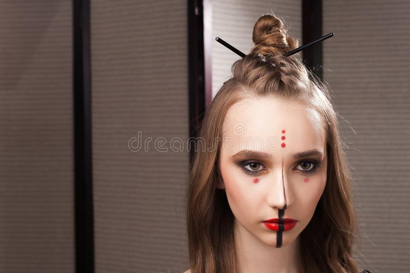 Model with unusual mystic makeup and coiffure. Beautiful young girl model with professional unusual mystic makeup and a coiffure with topknot and braid made by royalty free stock images