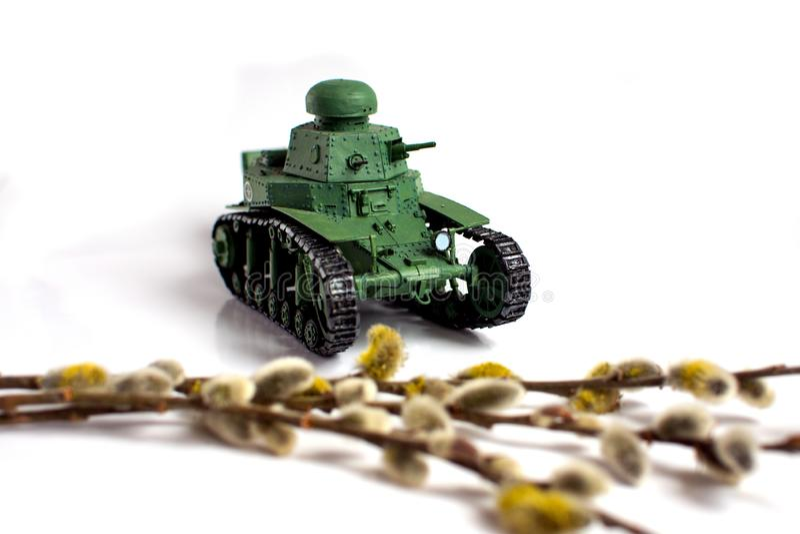 Model van een oude Sovjetdietank van document op een witte achtergrond wordt gemaakt Wilgentak in de voorgrond stock afbeeldingen
