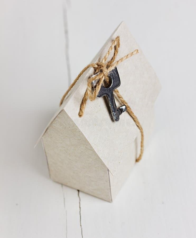Model van kartonhuis met een boog van streng en sleutel woningbouw, onroerende goederen lening, of kopend een nieuw huisconcept royalty-vrije stock fotografie