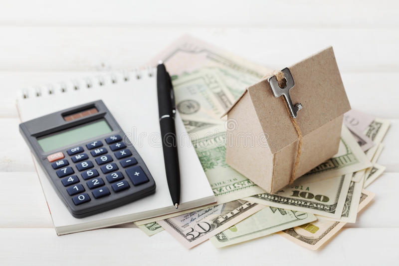 Model van kartonhuis met sleutel, calculator, notitieboekje, pen en contant gelddollars Woningbouw, onroerende goederen lening, stock fotografie