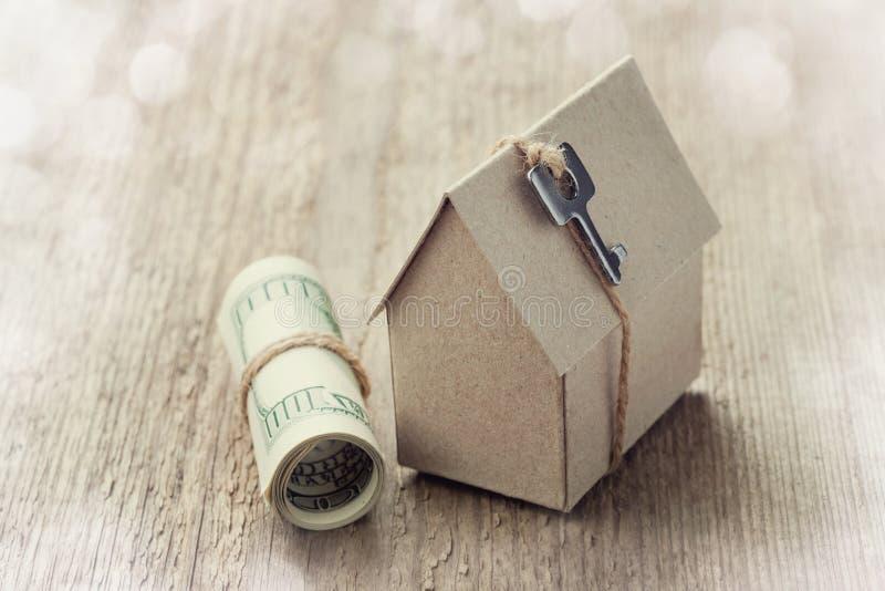 Model van kartonhuis met sleutel en dollarrekeningen Woningbouw, onroerende goederen lening, kosten om een nieuw huis te huisvest royalty-vrije stock afbeeldingen