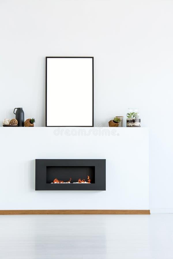 Model van lege affiche boven zwarte open haard in eenvoudige witte liv royalty-vrije stock afbeeldingen