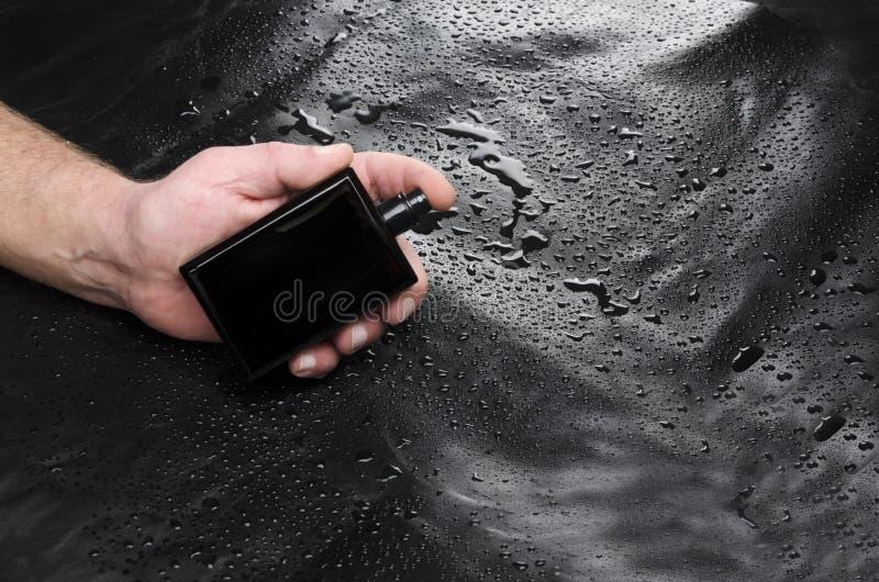 Model van totaal zwarte bootle met parfum tegen leerachtergrond De geur van de mensenholding stock afbeelding