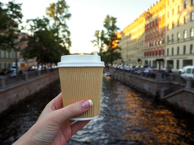 Model van vrouwelijke hand die een koffiedocument meeneemkop op de rivierachtergrond houden met exemplaarruimte royalty-vrije stock afbeeldingen