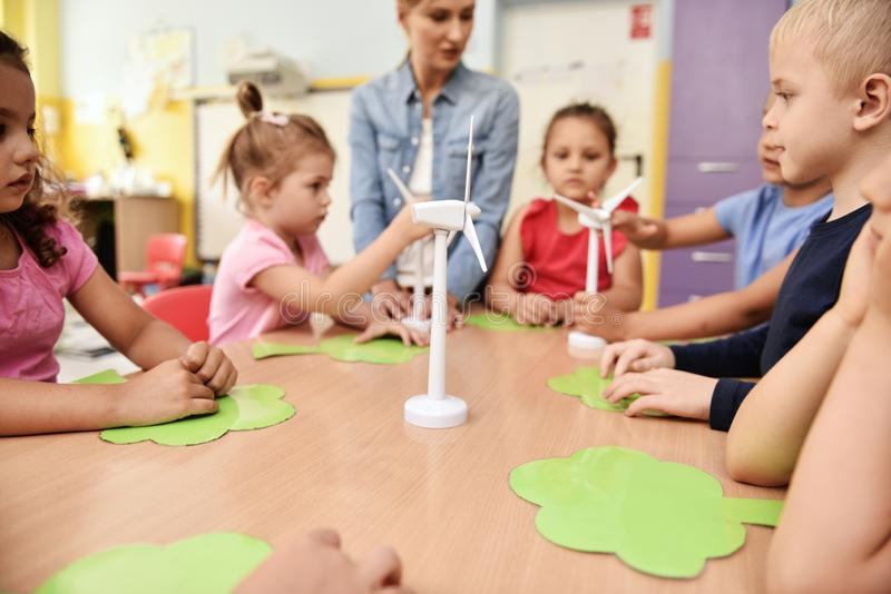 Model van windturbine en kinderen op de achtergrond stock fotografie