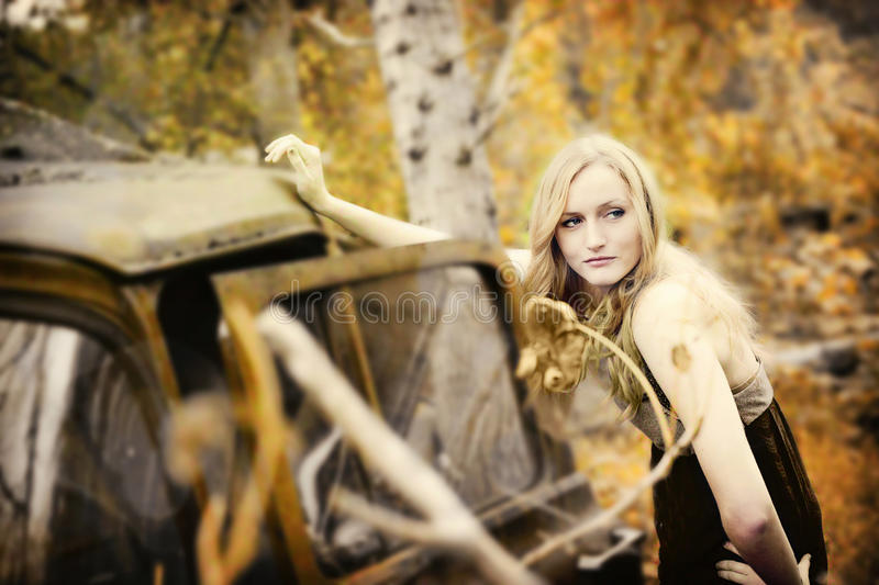 Model on vintage truck. A pretty blond woman leaning on an old abandoned truck in an autumn forest stock image