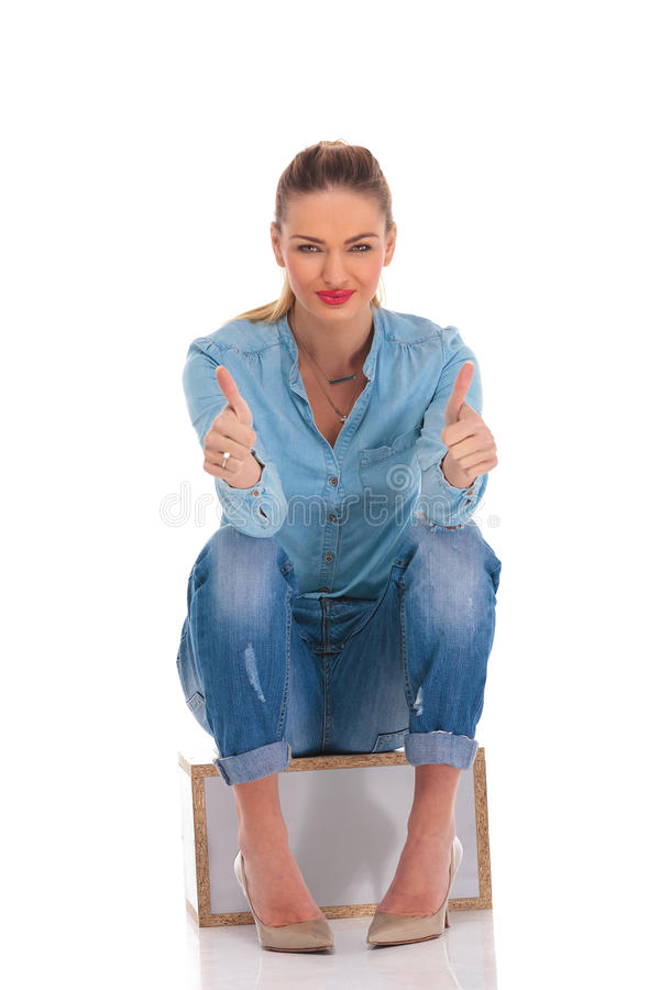 Model w drelichowej pozie sadzającej w pracownianym tle podczas gdy pokazywać vi fotografia stock