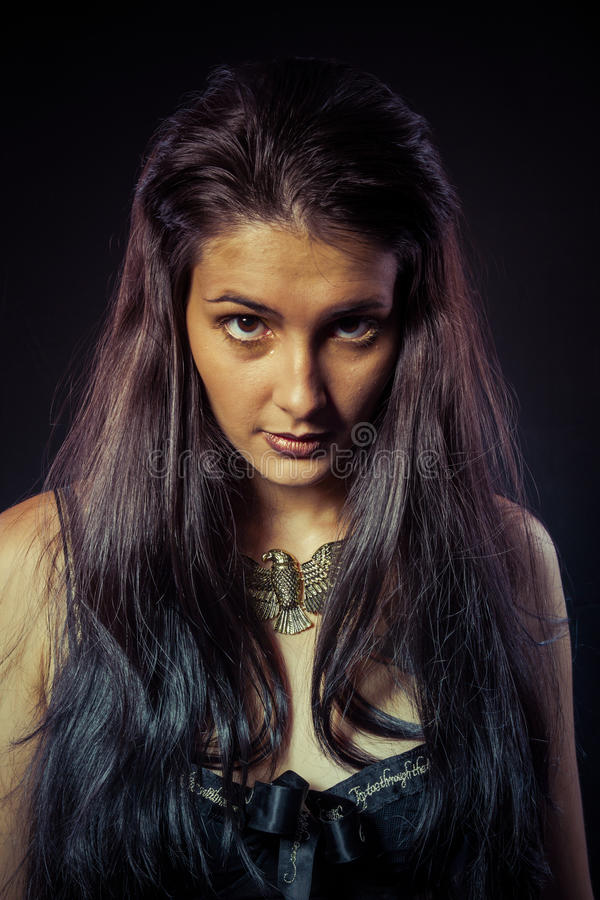 Model, Warrior woman with gold mask, long hair brunette. Long ha. Valkyrie, Golden statue concept. Arty portrait of model with golden mask and shiny lashes royalty free stock image
