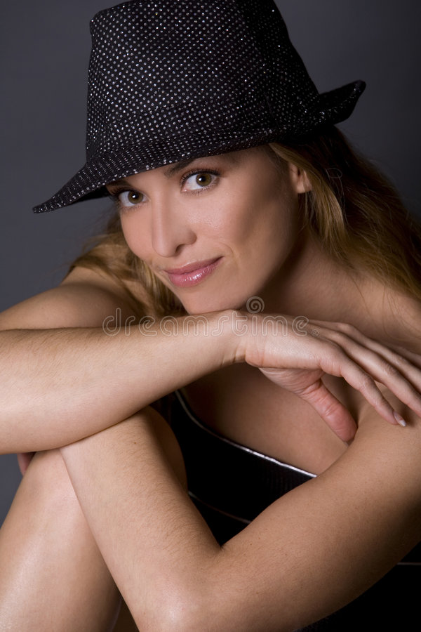Model wearing hat. Pretty woman wearing hat posing on dark background royalty free stock photography