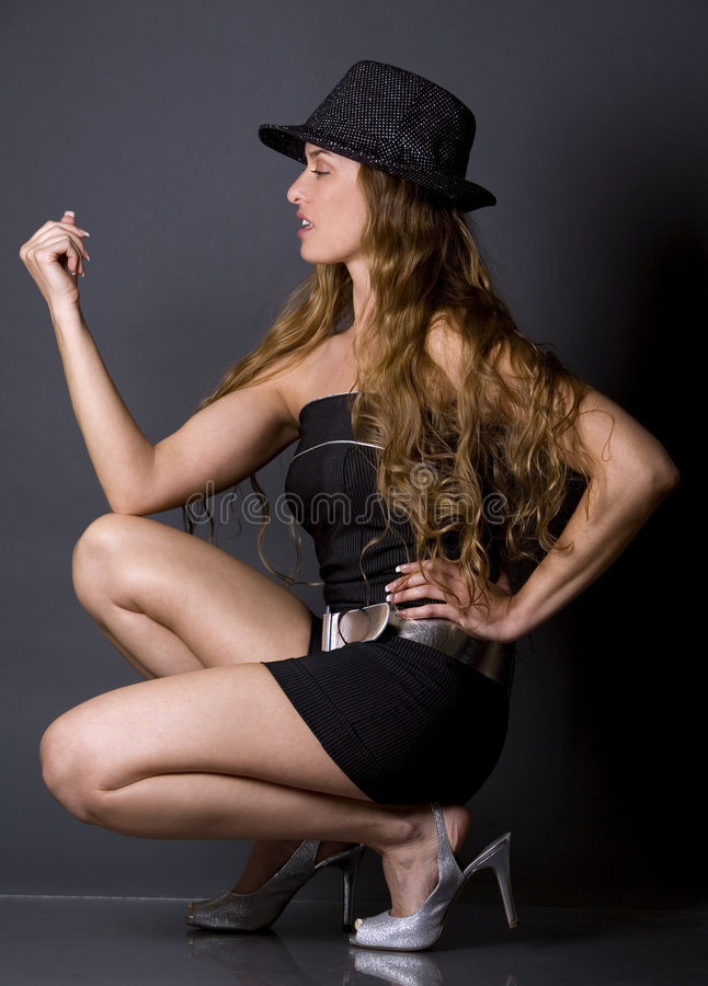 Model wearing hat. Pretty woman wearing hat posing on dark background royalty free stock images