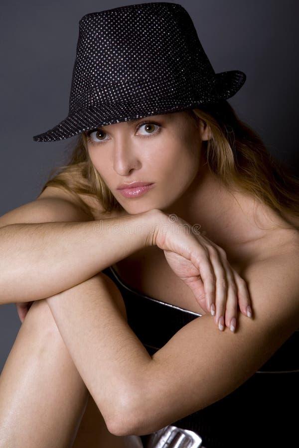Model wearing hat. Pretty woman wearing hat posing on dark background royalty free stock photo