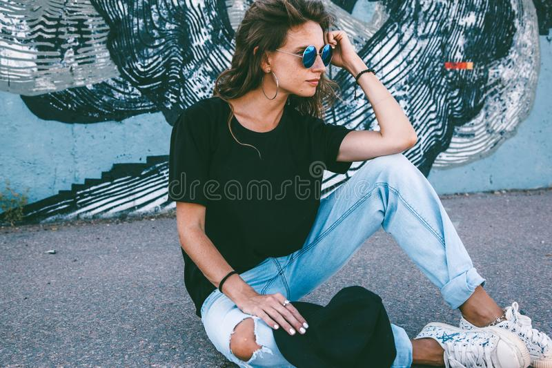 Model wearing plain tshirt and sunglasses posing over street wall royalty free stock images
