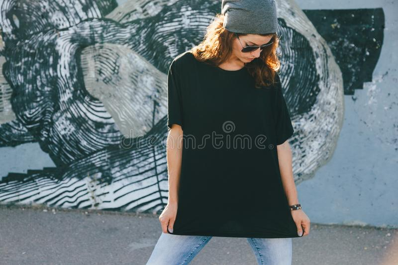Model wearing plain tshirt and sunglasses posing over street wall stock images
