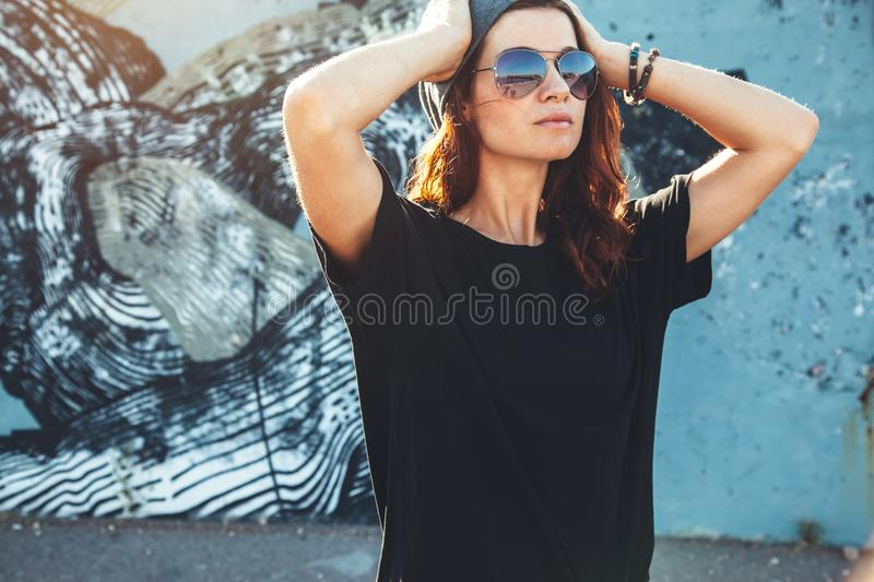 Model wearing plain tshirt and sunglasses posing over street wall stock photos