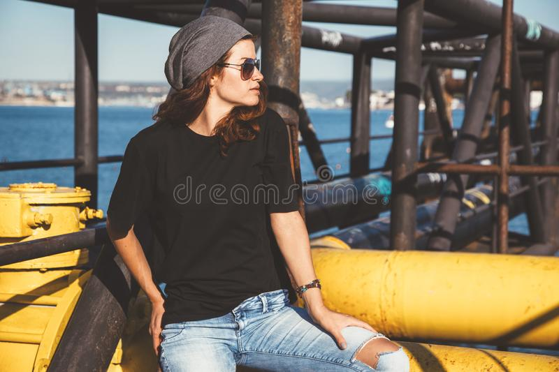 Model wearing plain tshirt and sunglasses posing over street wall royalty free stock photography