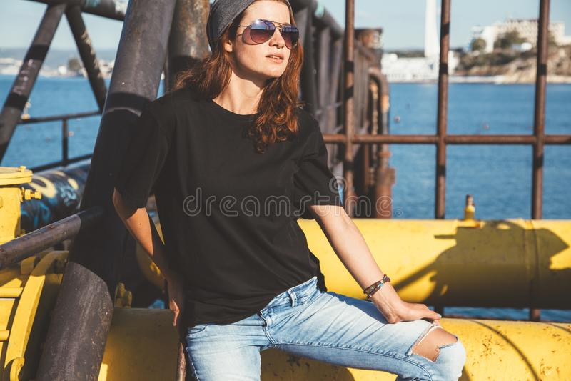 Model wearing plain tshirt and sunglasses posing over street wall royalty free stock image