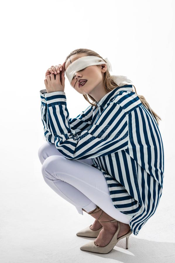 Model wearing white trousers and blouse wearing blindfold. Trousers and blouse. Blonde-haired model wearing white trousers and striped blouse wearing blindfold stock image
